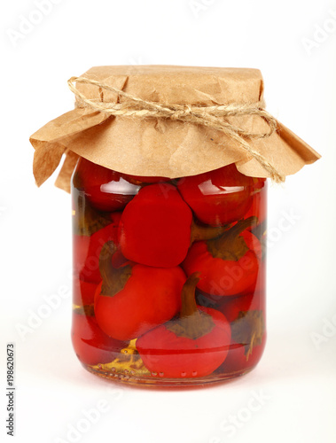 Fotobehang Hot chili peppers Jar of pickled red hot chili peppers over white
