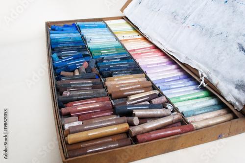 Odgórny widok duży pudełko barwioni pastele na ligt papierze. Pochmurny.