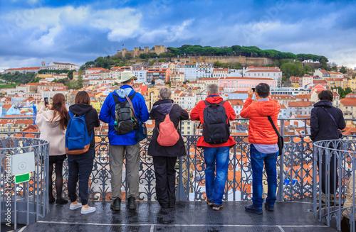 Grupa turyści ogląda pejzaż miejskiego Lisbon i bierze obrazki grodowa architektura w Portugalia