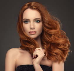 Beautiful model girl with long red curly hair .Red head . Care and beauty hair products  © edwardderule