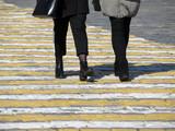 Women walk on a pedestrian crossing. Female feet on the pedestrian Zebra