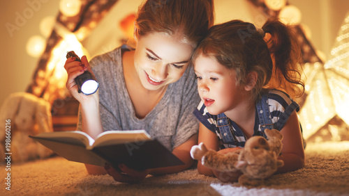 mother and child daughter reading a book and a flashlight before going to bed