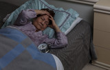 senior woman with headache during nighttime while in bed