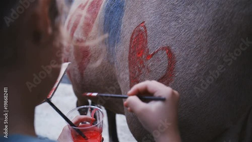 Child drawing a red love heart on horse close-up 4K