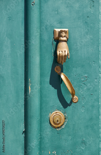 The old green door with the knocker in the shape of a hand. Mertola. Baixo Alentejo. Portugal