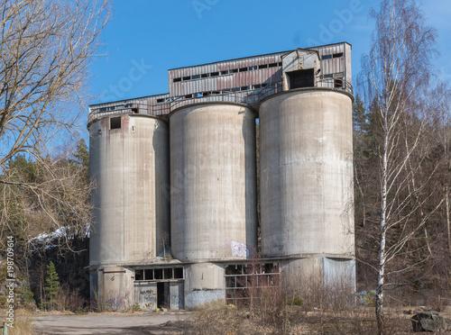 Fotobehang Oude verlaten gebouwen Abandoned silos from a closed cement factory located in Stora Vika, Sweden