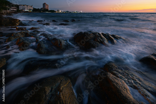 Foto op Plexiglas Zwart wave at the sea on the rock with sunset sky