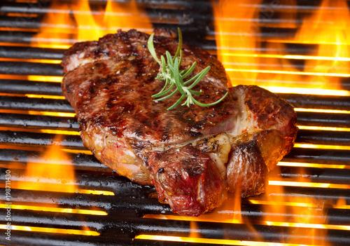 Foto op Plexiglas Steakhouse beef rib-eye steak is grilling on flame