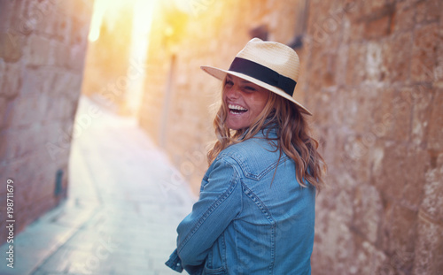Young stylish woman laughing on mediterranean street