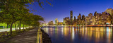 Panoramic view of Midtown Manhattan skyscrapers and the East River at twilight from Roosevelt Island promenade in Summer. New York City