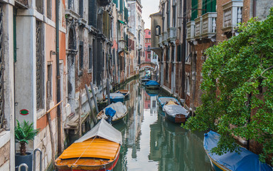 Small pretty canal with boats in Venice