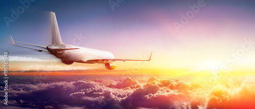 Fototapeta Airplane flying Above Clouds At Sunrise
