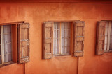 Facade of house with old windows with wooden shutters. Bologna, Italy - 198772696