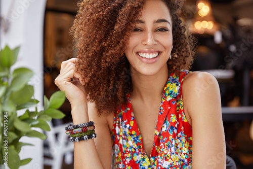 Portrait of good looking happy dark skinned female with curly hair and shining broad smile, demonstrates positive emotions, wears stylish bright blouse. People, ethnicity and beauty concept.