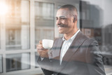 Waist up portrait of handsome businessman looking into the distance with happy smile while savour cup of tea. Man is on the other side window of cabinet - 198776071