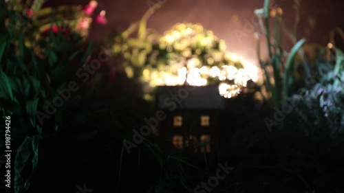 Slider shot. Fantasy night decoration. Small beautiful house in grass with light. Old house in forest at night with moon. Dark foggy lighted background. Selective focus