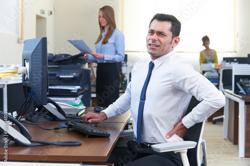 Businessman Working At Desk Suffering From Backache