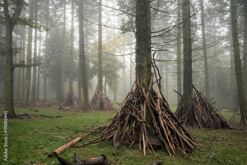 Den building area for children in forest landscape on foggy Autumn morning
