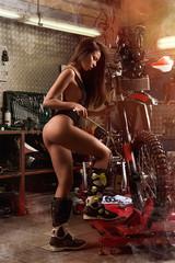 Sexy girl repairing motorcycle