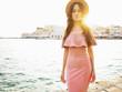 Stylish brunette woman enjoying sunrise on seafront
