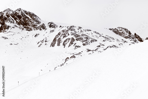 Minimalist mountain landscape. Ski trail and rock in the snow - 198826447