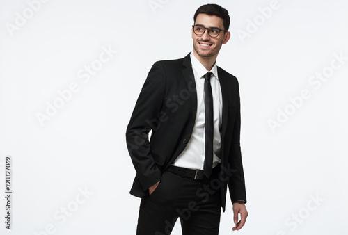 Młody biznesowego mężczyzna odprowadzenie w studiu, robi krokowi, będący ubranym formalnego kostium, odizolowywającego na popielatym tle
