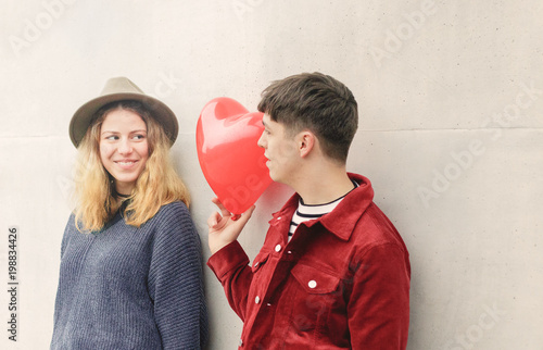 Young man gives a heart-shaped balloon to his blonde girlfriend for the Valentin Poster
