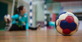 Handball ball on court floor. Blurred female goalkeeper background. Space for text, close up view.