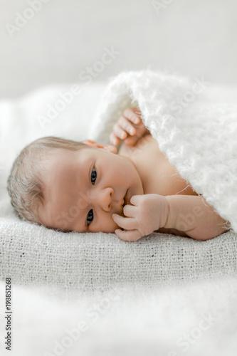 portret noworodka na białym pled.