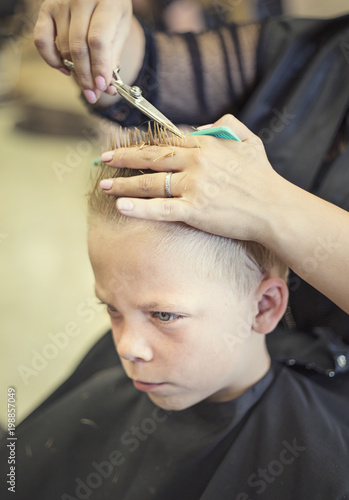 A cute young blonde boy getting his hair cut at a beauty salon or barbershop by a female hair stylist