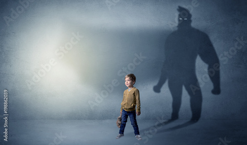 Foto Murales Cute kid in a room with plush on his hand and hero shadow on his background