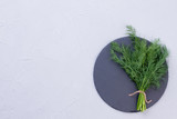 Fresh bunch of dill on round slate. Branches of green dill herbs on stone stand and copy space, top view. - 198864291