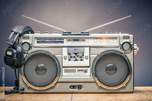 Retro outdated portable stereo boombox radio cassette recorder from circa late 70s with aged headphones front gradient black wall background. Listening music concept. Vintage old style filtered photo - 198866228