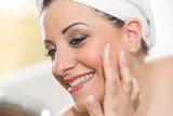 Portrait of smiling young woman applying moisturizing cream - 198871612