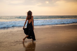 Young beautiful woman has fun at the ocean in summertime
