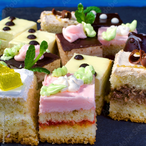 Assorted colorful natural sweet cakes on a black background. Concept of tasty cakes. Food background.