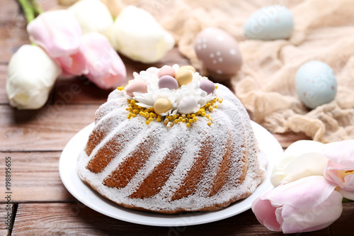 Easter cake with eggs and tulip flowers on wooden table