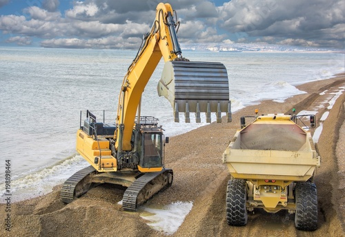 Fototapeta Construction - Heavy Machinery Construction Site - Engineering - Sea Defence. Large plant machinery being use to build the beach sea defence at Seaford, East Sussex, UK