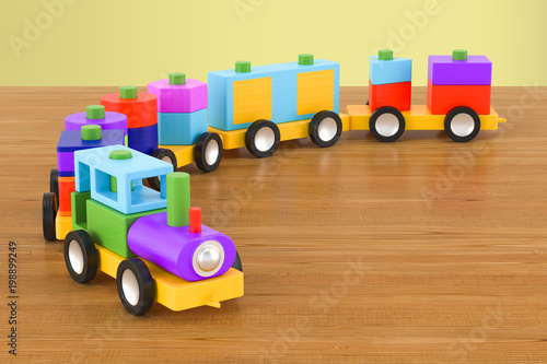Fototapeta Wooden toy train with colorful blocs on the wooden table. 3D rendering