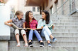 Three teenage girls sitting outdoors at the steps and discussing books