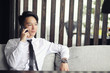 A young Asian businessman is waiting for a partner in a cafe. Bu