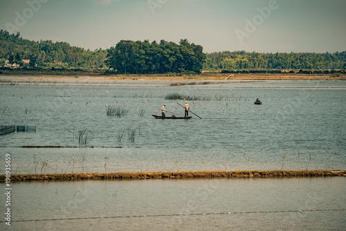Fotobehang Donkergrijs two fisherman fishing on a lake in vietnam