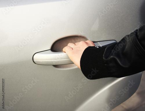 ręka mężczyzny otwiera drzwi szarego nowoczesnego samochodu, fragment samochodu.
