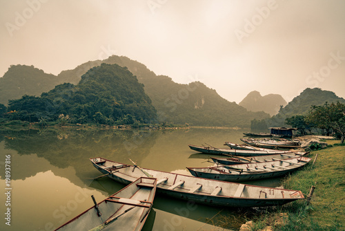 Foto op Canvas Beige rafts await villagers by the lake in Vietnam
