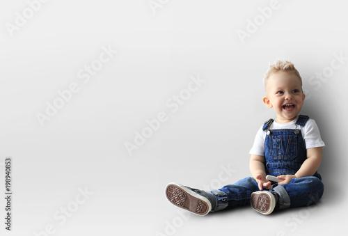 Little boy in denim overalls is smiling