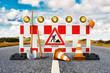 Leinwandbild Motiv Baustelle, Absperrung, Straßensperrung mit Schaufel, Pickel, Baustellenschild, Pylone und Sicherheitshelm auf Straße