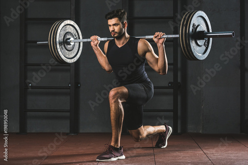 Poster Young sportsman doing exercise with barbell on shoulders in gym