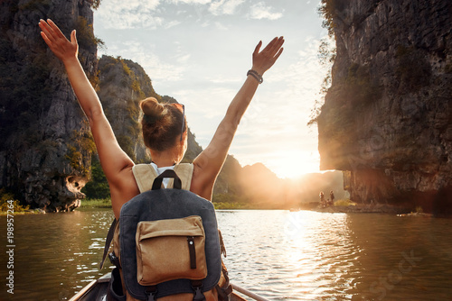 joyful woman traveler with backpack enjoying view at the of karst mountains at sunset.