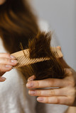 Woman trying to brush tangled hair ends