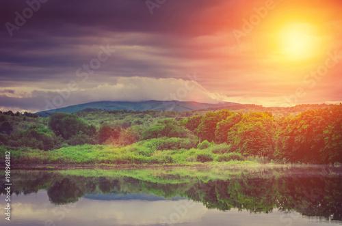 Canvas Oranje eclat beautiful lake sunset, behind mountain forest